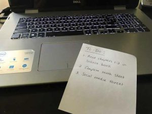 note with an active thread on top of a laptop, social media threats